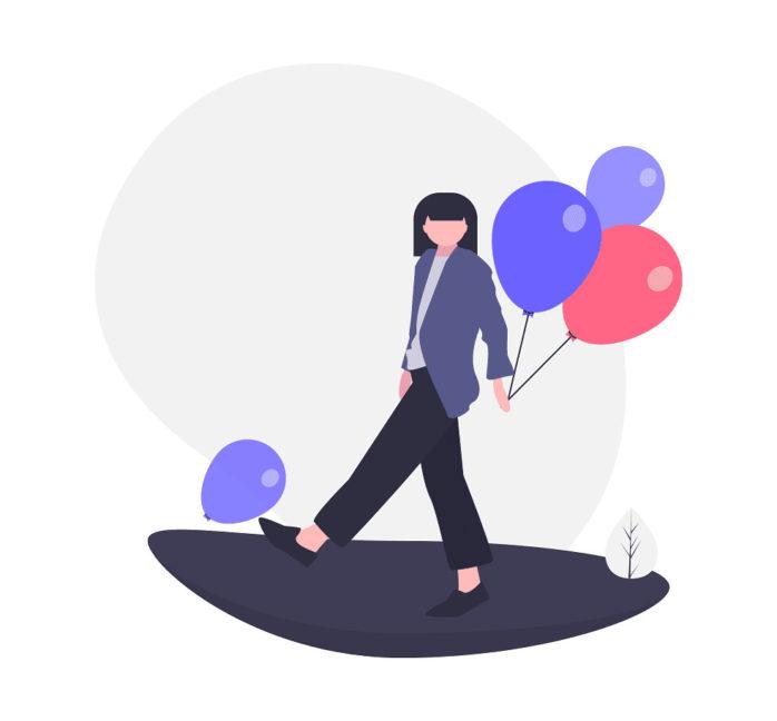 風船を3つ持って歩く女性の画像。