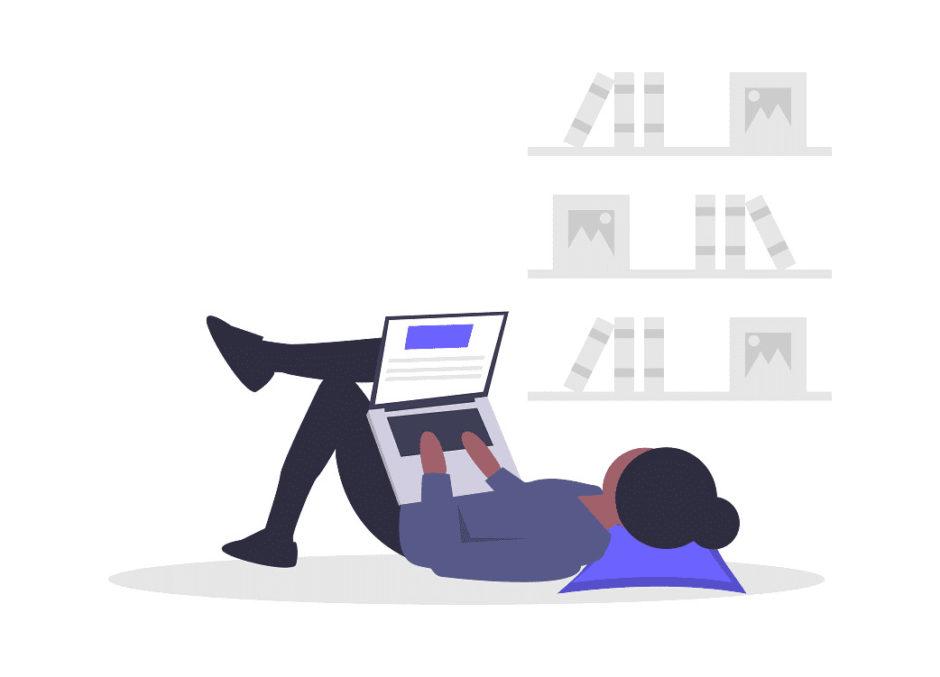寝転がりながらパソコンを使う男性の画像。
