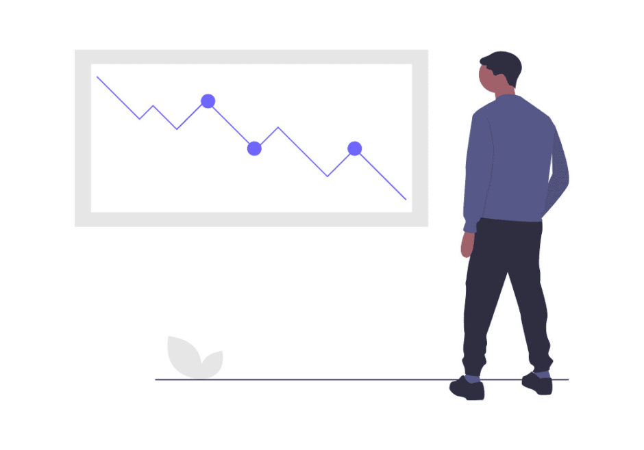 下がるベアマーケットのデータを見る男性の画像。