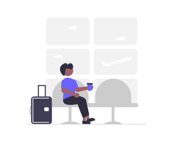 空港で時間を待つ男性の画像。